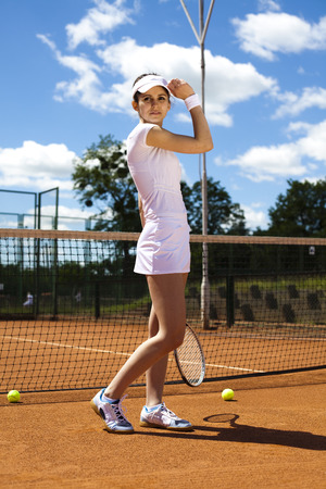 Girl playing tennis on the court photo