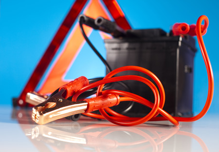 12v: Car battery with two jumper cables clipped Stock Photo