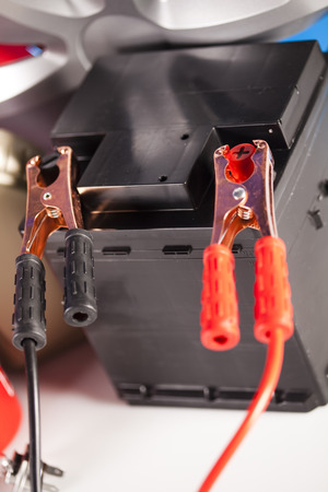 12v: Car battery with two jumper cables clipped on vivid moto concept Stock Photo