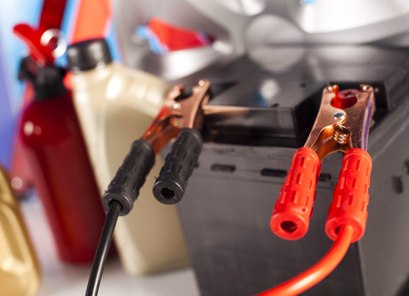 nipples: Car battery with two jumper cables clipped on vivid moto concept Stock Photo