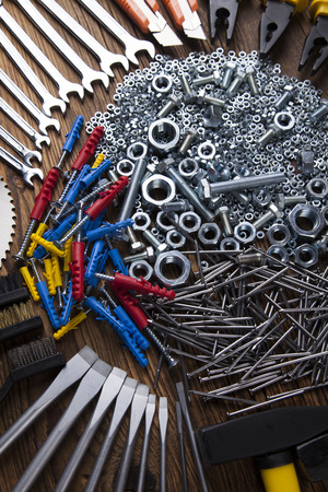 triplet: Assorted work tools on wood background