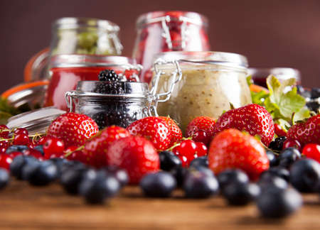 jams: Jams in glass jars with wood and fresh berries