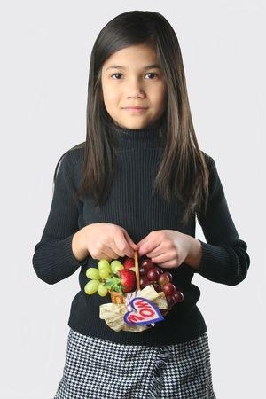 carying: Child with mini fruit basket  Stock Photo