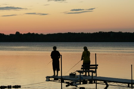 Two children fishing off pier at sunset. photo