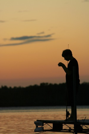 Silhouette of a boy against sunset as he fishes on the pier. photo