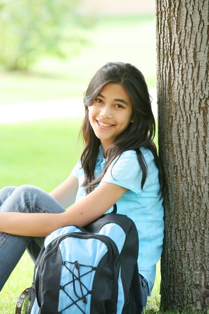 scandinavian descent: Beautiful young teen sitting beside a tree on her first day of school. Stock Photo