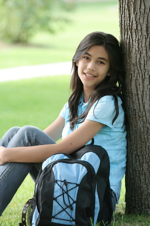 Teenage girl sitting against tree,ready for first day of school.