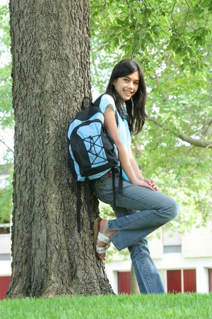 first day: Young teenage girl ready for high school;backpack on standing in front of school.