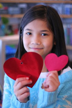 nine years old: Nine year old girl holding up two red hearts.