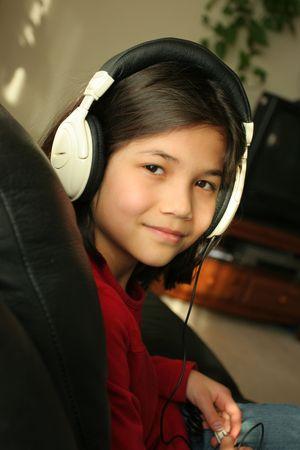 scandinavian descent: Nine year old girl listening to music with headphones. Part ASian, Scandinavian descent.
