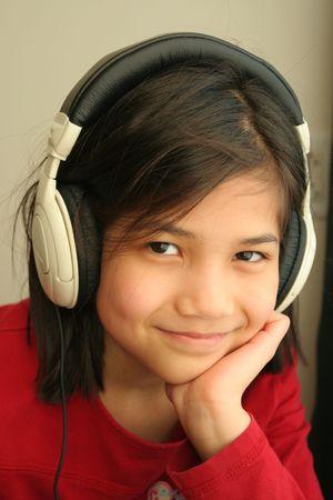 scandinavian descent: Listening to music on the headphones. Part asian, scandinavian descent.