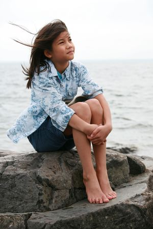 scandinavian girl: Nine year old girl sitting by lake in summer. Part asian- Scandinavian background.