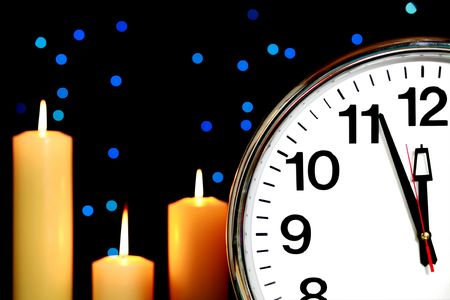 12 o'clock: Clock set at three minutes to midnight with blue Christmas lights in background and candles burning
