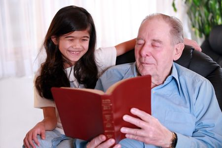 Elderly man and little girl reading Bible together, great grandpa and great granddaughter. photo