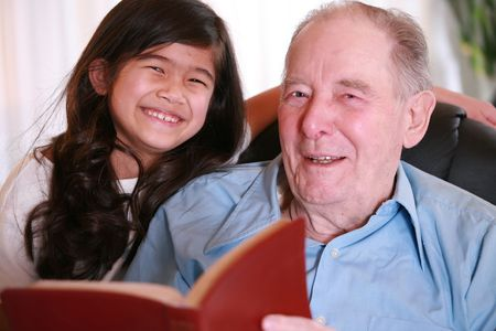 Elderly man and little girl reading Bible together, great grandpa and great granddaughter. Stock Photo - 4478791