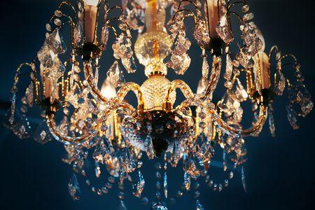 chandelier: Elegant crystal chandelier hanging against blue background Stock Photo