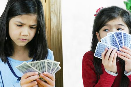 children at play: Two girls playing cards, one is cheating and looking at the others hand