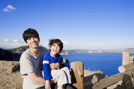 special needs: Big brother holding smiling disabled little boy with Oregon Stock Photo