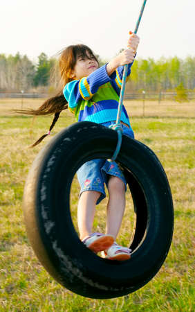 summer tire: Little girl swinging on tire swing in the countryside