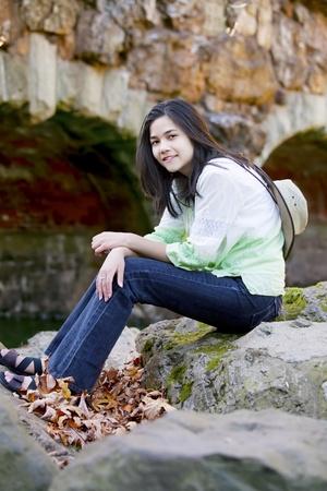 Biracial teen girl relaxing on rocks by stone bridge Stock Photo - 17034310