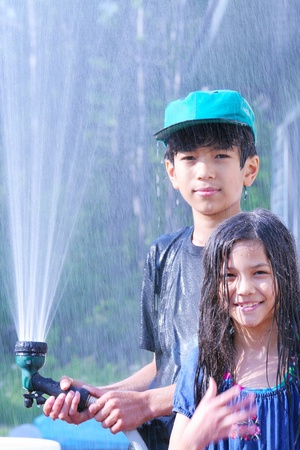 Brother and sister playing with water hose photo