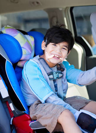 Handsome disabled six year old boy smiling in carseat photo
