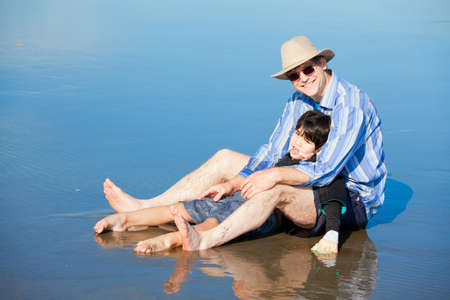 Father playing with disabled son on beach, holding him upright. Child has cerebral palsy