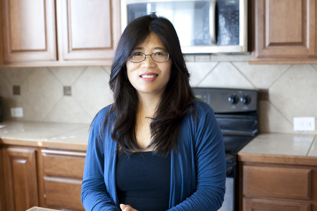 early forties: Beautiful Asian woman in early forties standing in kitchen, stove and cabinets in background