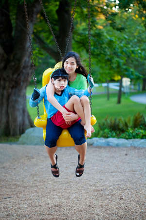 cerebral palsy: Big sister holding disabled brother on special needs swing at playground in park. Child has cerebral palsy.
