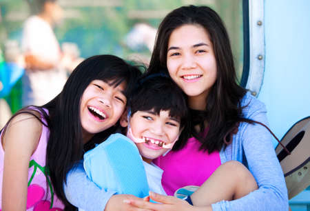 mixed race teen: Two sisters taking care of disabled little brother. Child has cerebral palsy Stock Photo