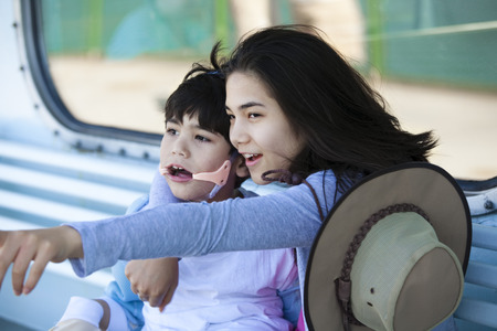 cerebral palsy: Teen sister taking care of disabled little brother, pointing off camera. Child has cerebral palsy. Stock Photo