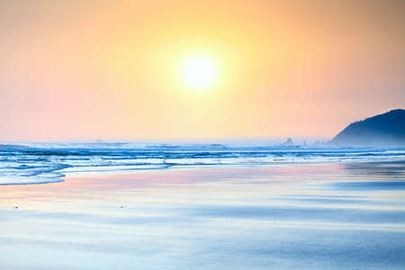 late summer: Beautiful yellow orange sunset over   gentle waves washing up on beach Stock Photo