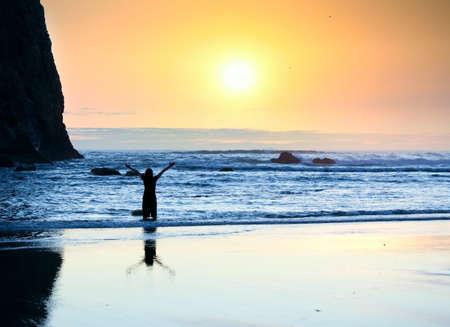 alabando a dios: Silueta de la muchacha que se coloca en las olas, los brazos levantados en la alabanza a Dios al atardecer