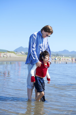 cerebral palsy: Father helping disabled son walk in the ocean waves on beach. Child has cerebral palsy. Stock Photo
