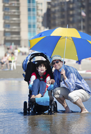Father holding umbrella over disabled son in wheelchair at the beach Stock Photo - 22478223