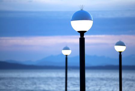 lamp posts: Lamp posts lit at night with blue mountain background and lake scene at dusk
