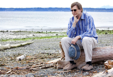 Depressed, sad Caucasian  man in forties sitting on driftwood on beach, chin in hand