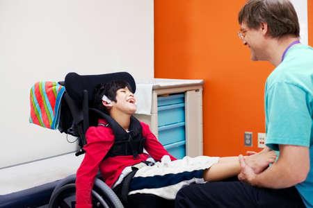 ni�o discapacitado: Muchacho lisiado en el intercambio de risa silla de ruedas con su m�dico o terapeuta