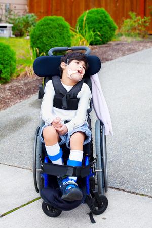 Zeven jaar oude biracial gehandicapte jongen in een rolstoel. Kind heeft hersenverlamming.