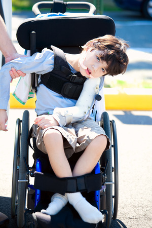Young disabled child in wheelchair. Child has cerebral palsy. Stock Photo