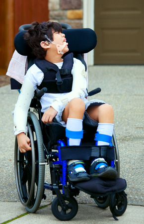 prosthetics: Seven year old biracial disabled boy in wheelchair. Child has cerebral palsy.