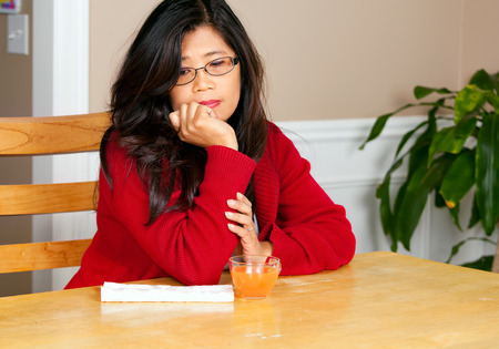 long depression: Asian woman relaxing at dining table with glass of juice, sad or lonely expression