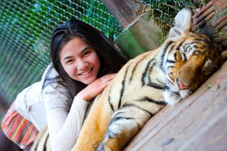 tiger cub: Biracial teen playing with sleeping tiger cub in Thailand