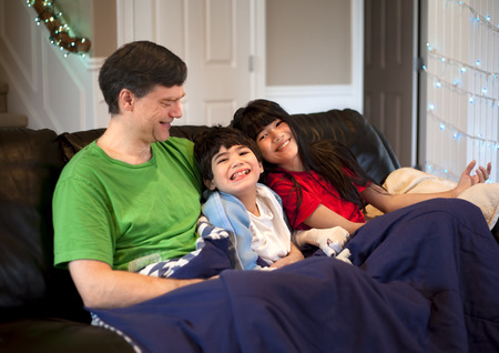 cerebral palsy: Father sitting on couch with daughter and disabled son. Son has cerebral palsy.