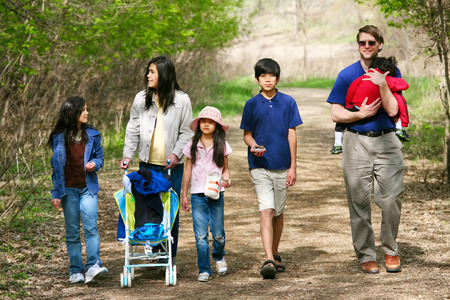 Family walking along quiet country path through woods photo