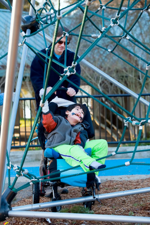 jungle gym: Father with disabled boy at the playground jungle gym