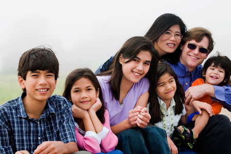 Multiracial family of seven sitting on foggy beach