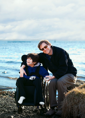 Father sitting with disabled son in wheelchair by lake shore photo