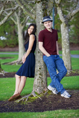 Young happy interracial couple standing together  by tree photo