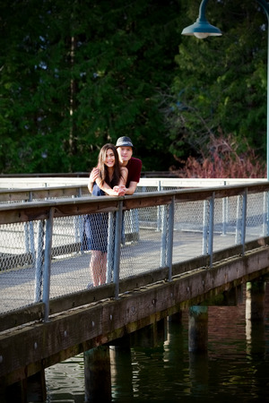 Happy young interracial couple standing on bridge over water photo